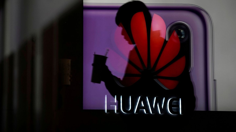 Un hombre pasa por detrás de un escaparate con un anuncio de Huawei en Shanghai, en diciembre de 2018. (Reuters)