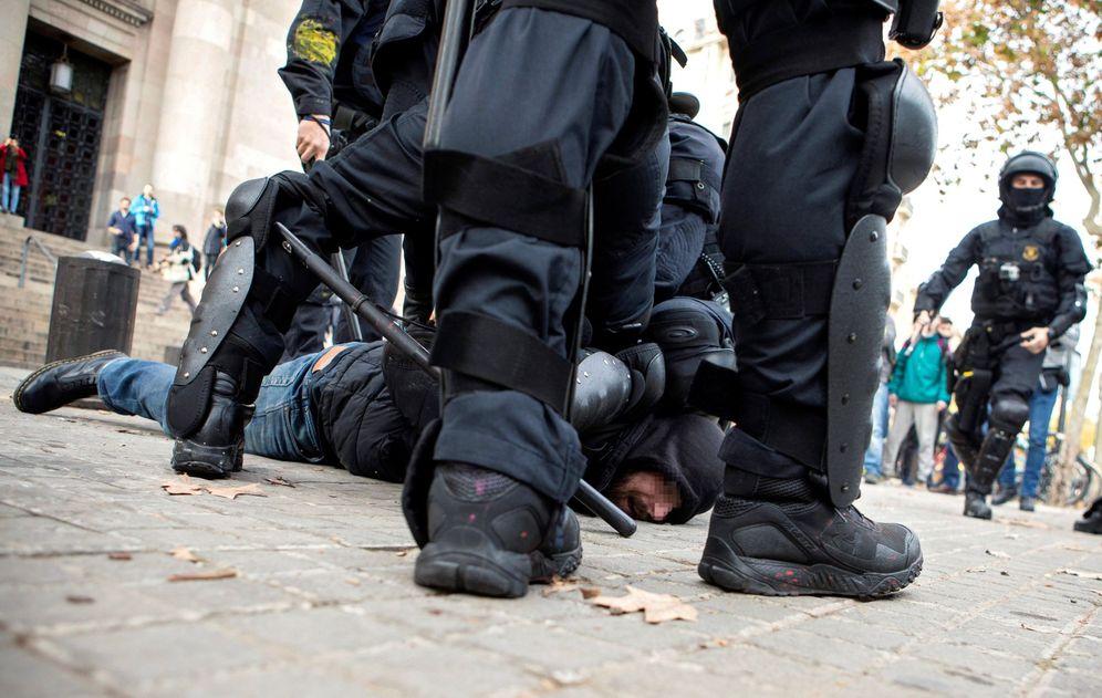 Foto: Efectivos de los Mossos d'Esquadra detienen a un simpatizante independentista en las inmediaciones de la Llotja de Mar de Barcelona el pasado viernes. (EFE)