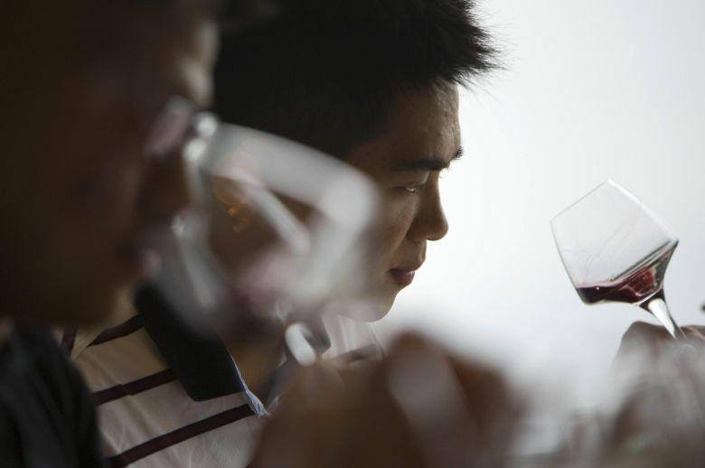 Dos hombres prueban un vaso de vino español durante una feria en Hong Kong (Reuters).