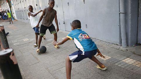 Niños juegan a fútbol en una calle de Monrovia (Liberia)