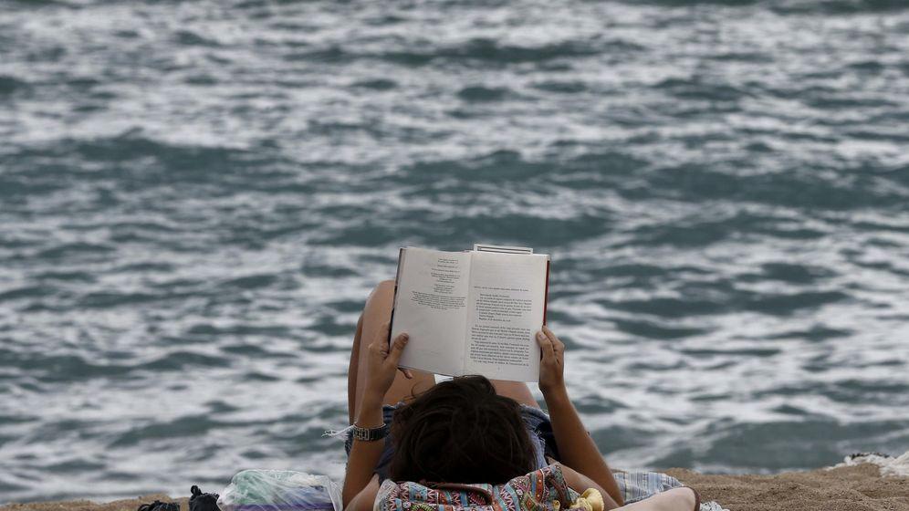 Foto: Una joven disfruta de la lectura de un libro en la playa de la Barceloneta. (EFE)