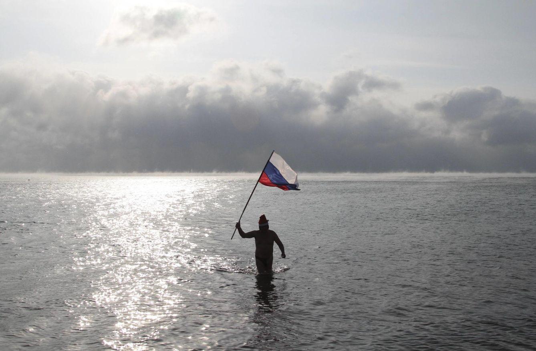 Foto: Un hombre sostiene una bandera rusa mientras sale de las frías aguas del Mar Negro en Yevpatoriya, Crimea (Reuters).