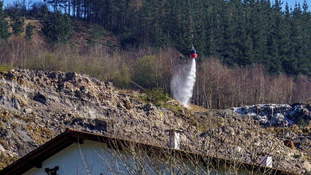 Un helicóptero lanza espuma sellante al vertedero de Zaldibar para controlar fuegos