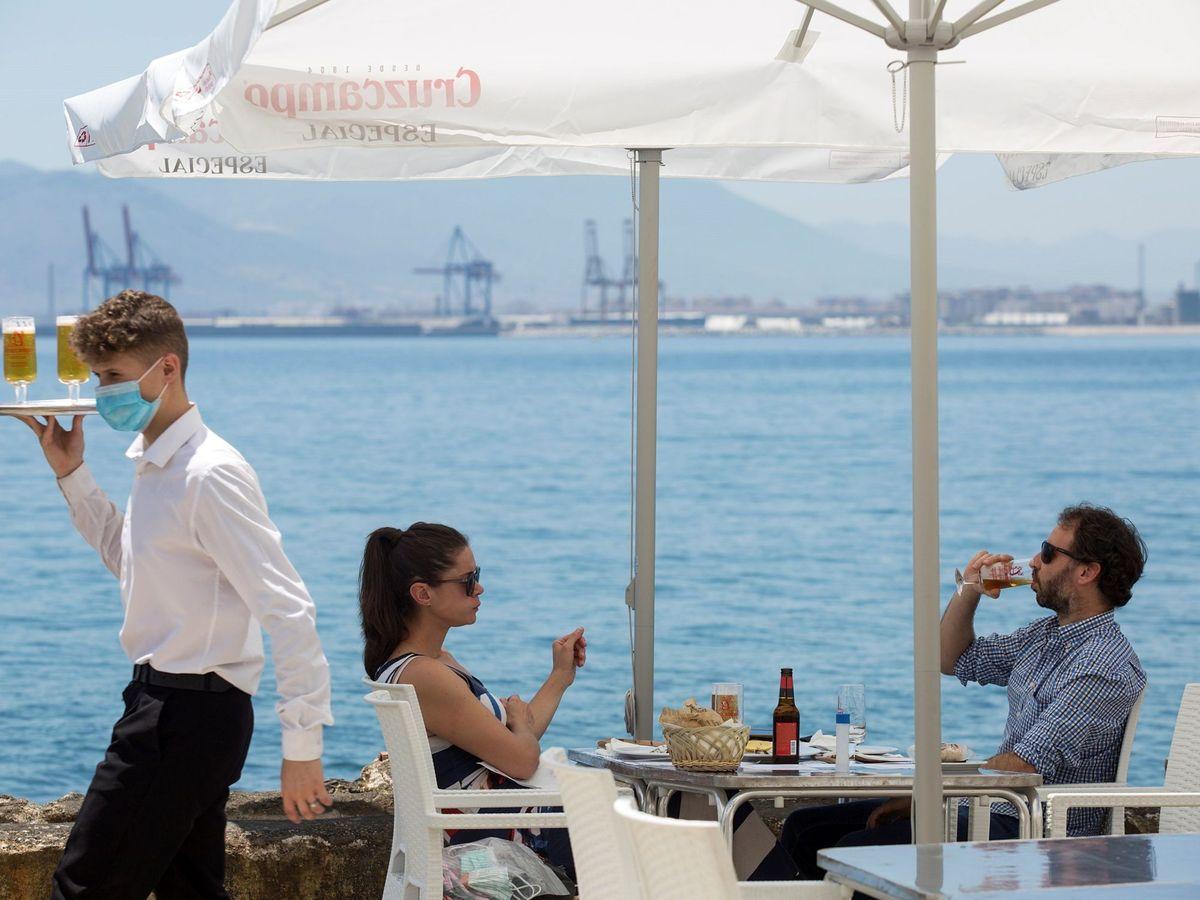 Foto: Un camarero con mascarilla pasa ante una pareja que almuerza en un restaurante de Málaga. (EFE)