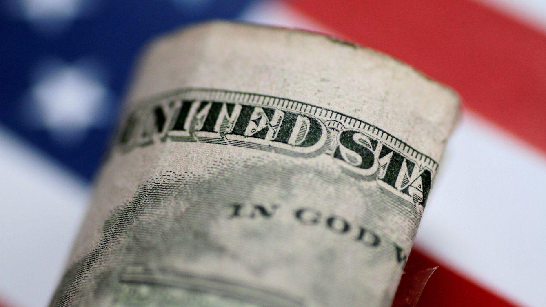Foto: Un billete de 5 dólares frente a una bandera estadounidense. (Reuters)