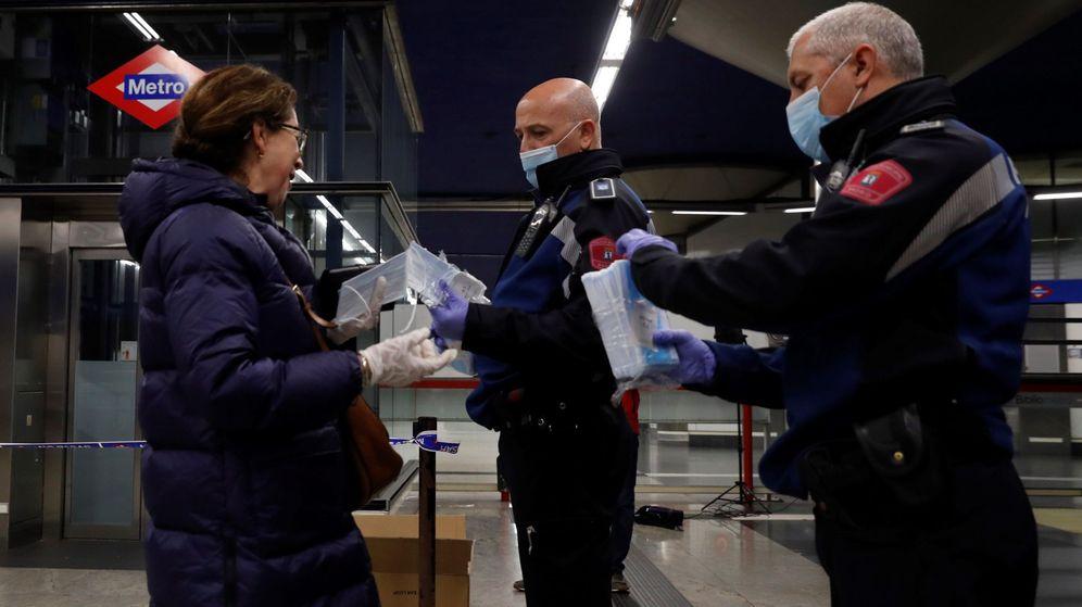 Foto: Dos policías reparten mascarillas en el metro de Madrid el pasado 13 de abril. (EFE)