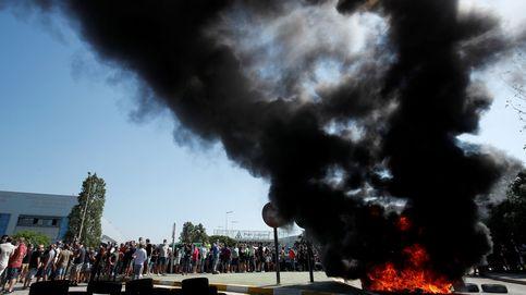Los trabajadores cortan la carretera y queman neumáticos ante la sede de Nissan