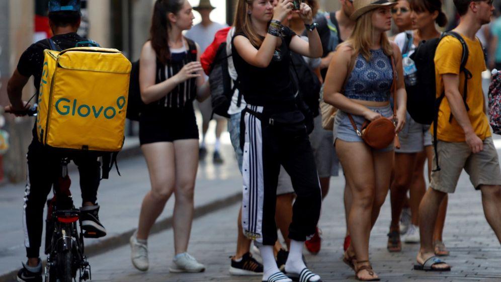 Foto:  repartidor de Glovo circula entre turistas en el centro de Barcelona. (EFE)