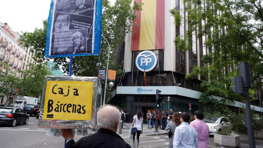 Foto: Un hombre se manifiesta delante de la sede del Partido Popular, en la calle Génova de Madrid. (EFE)