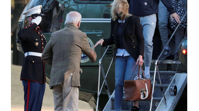Joe Biden ayuda a Jill Biden (que lleva un bolso de Valentino) a bajar del avión. (Reuters)