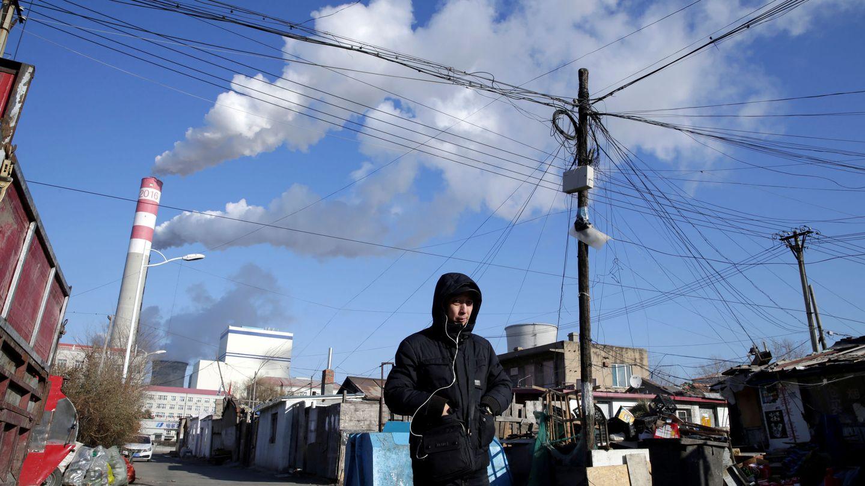 Un hombre camina cerca de una central de carbón, en la ciudad china de Harbin. (Reuters)