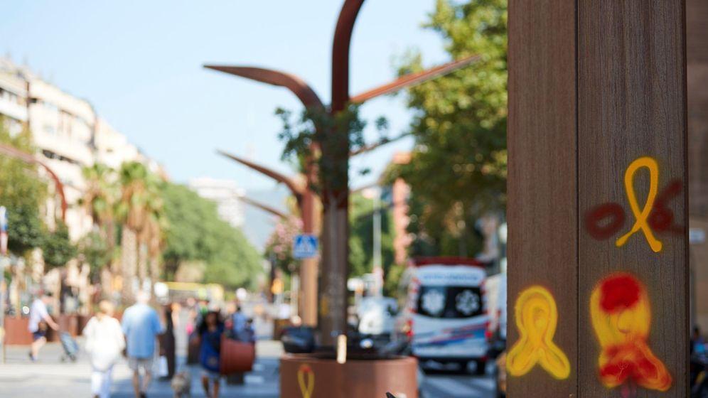 Foto: Lazos amarillos pintados con rojo por encima en el barrio de Sants. (EFE)