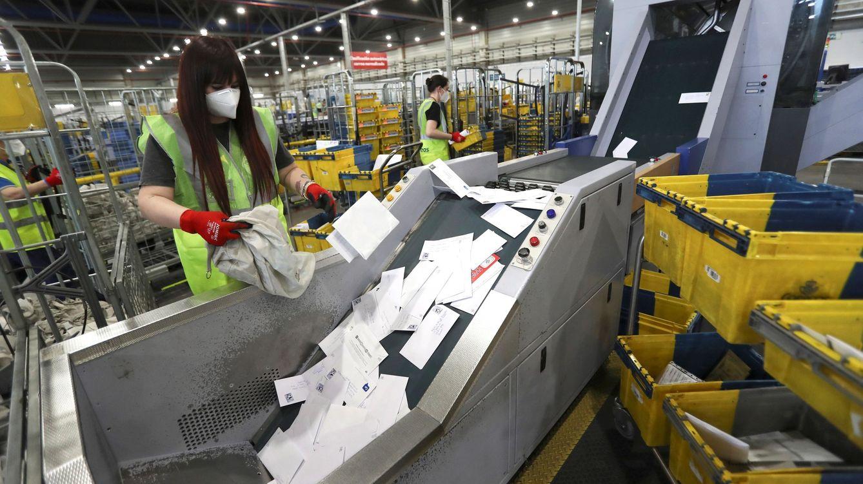 Foto: Operarios de Correos gestionan envíos en el CTA de Vallecas, Madrid. (EFE)