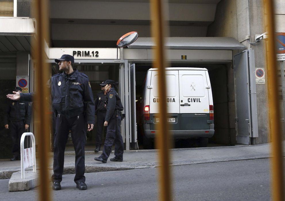 Foto: Policias nacionales aguardan junto a un furgón en la puerta de la Audiencia Nacional. (EFE)