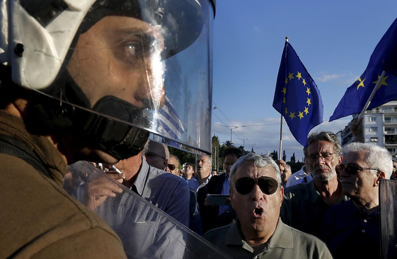 Foto: Un policía griego entre manifestantes proSyriza y proeuropeos durante protestas en Atenas, el 22 de junio de 2015 (Reuters).