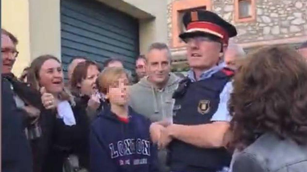 Foto:  Uno de los mossos informa a los votantes de la orden que tienen de entrar. (EC)