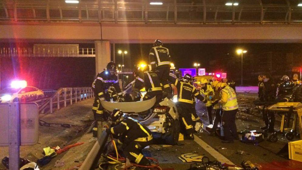 Foto: Los bomberos tratan de sacar al conductor atrapado en el vehículo. (Emergencias Madrid)
