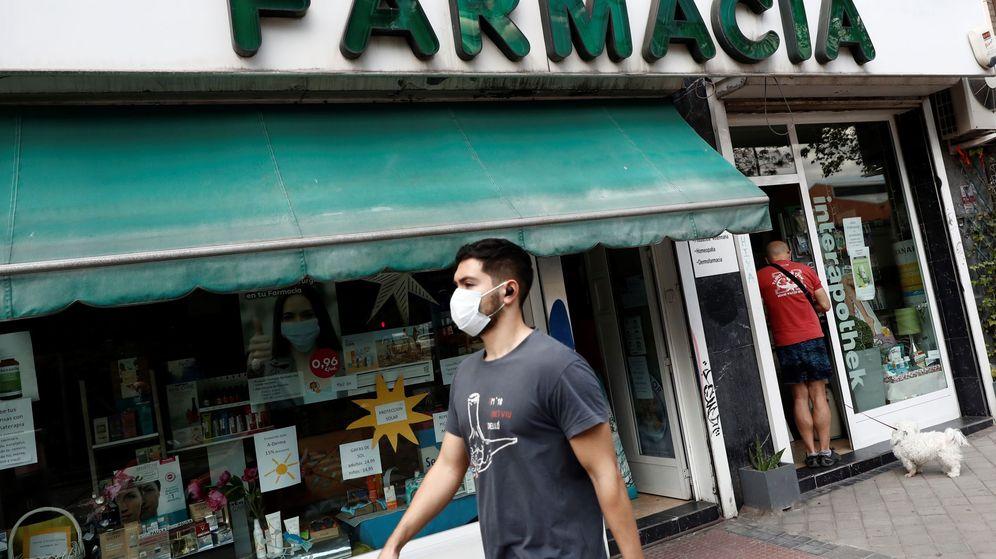 Foto: Un hombre pasea frente a una farmacia en Madrid. (EFE)