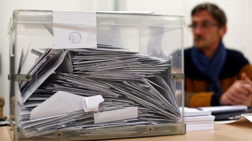 Foto: Un miembro de una mesa electoral, sentado tras una urna. (Reuters)