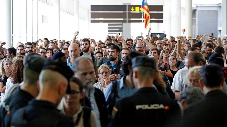 Agentes de los Mossos d'Esquadra y de la Policía Nacional controlan el acceso a la T1 del Aeropuerto de El Prat. (EFE)