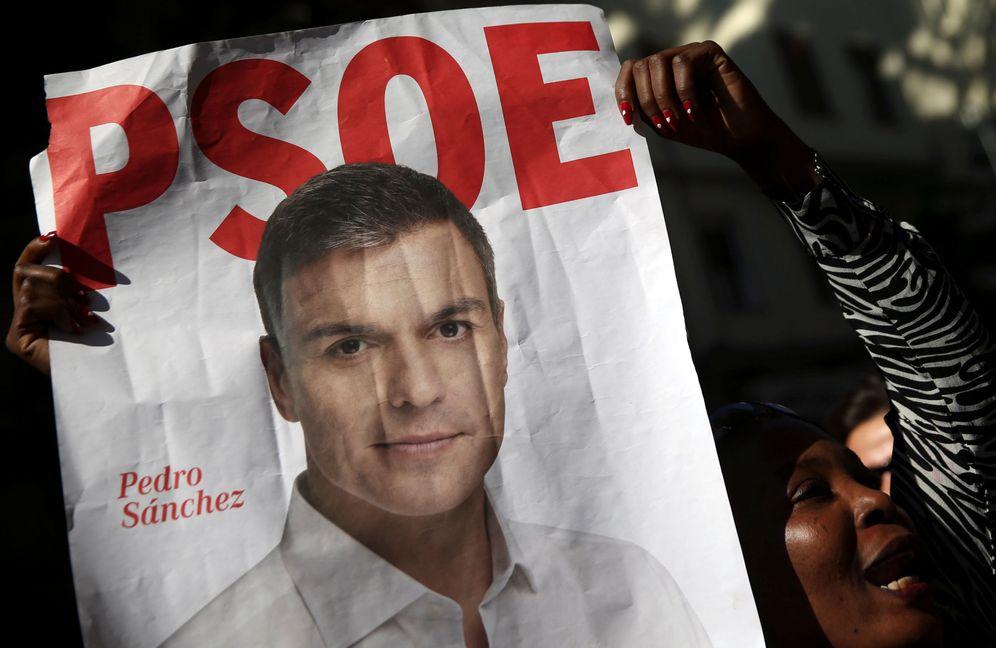 Foto: Un simpatizante del PSOE muestra uno de los carteles electorales de Pedro Sánchez como candidato a La Moncloa, el pasado 1 de octubre. (Reuters)
