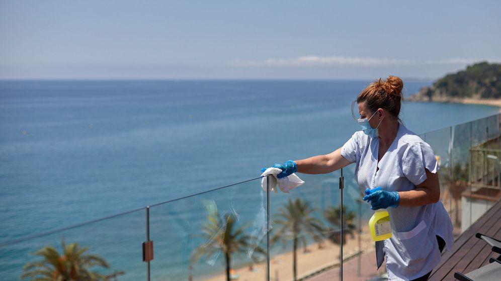 Foto: Una mujer desinfecta una barandilla de cristal por el covid-19. (EFE)