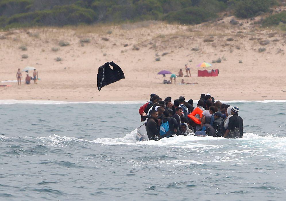 Foto: Un migrante arroja un chaleco salvavidas cuando la patera en la que viaja se aproxima a una playa de Tarifa, el 27 de julio de 2018. (Reuters)