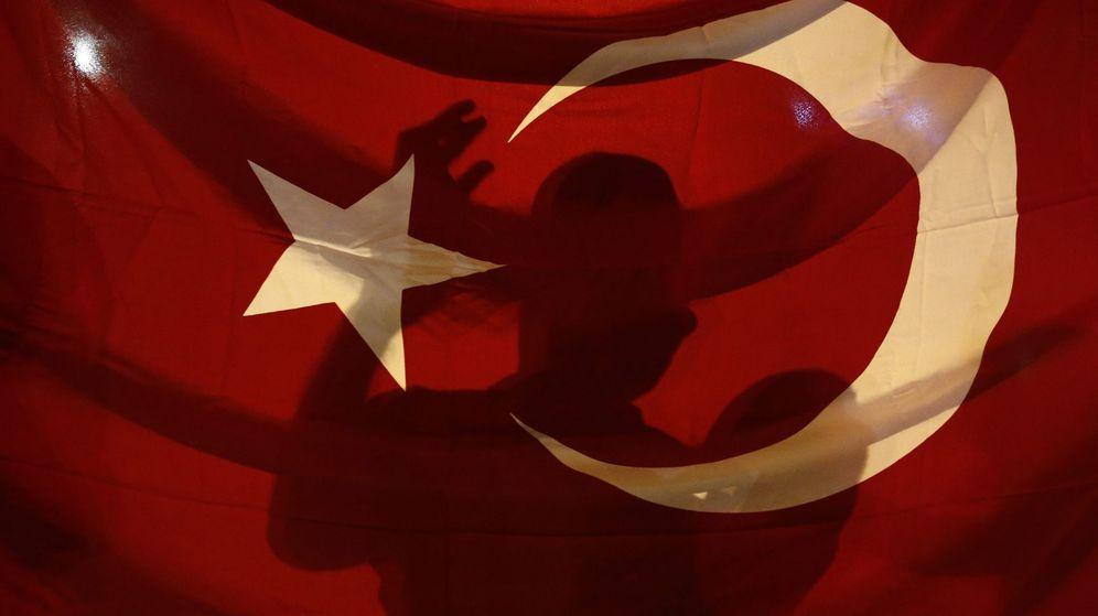 Foto: Un simpatizante de Erdogan grita consignas tras la bandera. (Reuters)