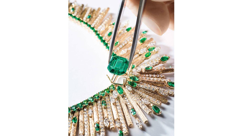 Foto: Momento del engaste de una enorme esmeralda en un collar de oro amarillo, diamantes y esmeraldas.