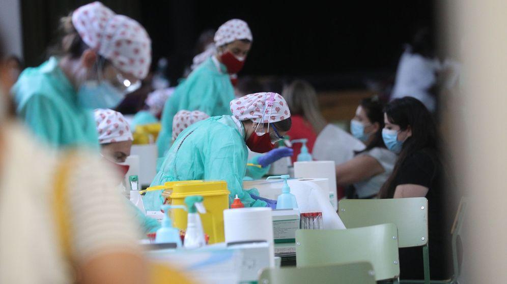 Foto: Personal sanitario realiza test de anticuerpos a los cientos de profesores y personal que trabaja en los centros de educación, en el IES Virgen de la Paloma. (EFE)