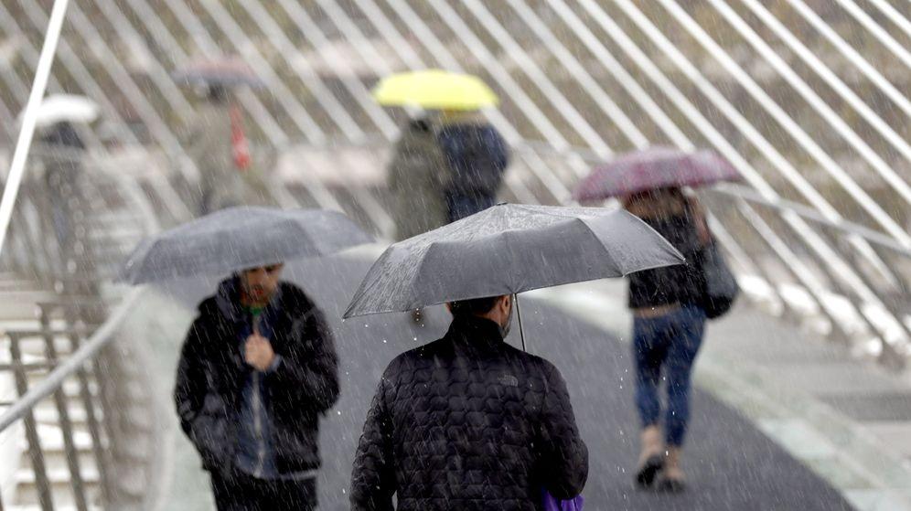 Foto: Varias personas se protegen de la lluvia en Bilbao. (EFE)