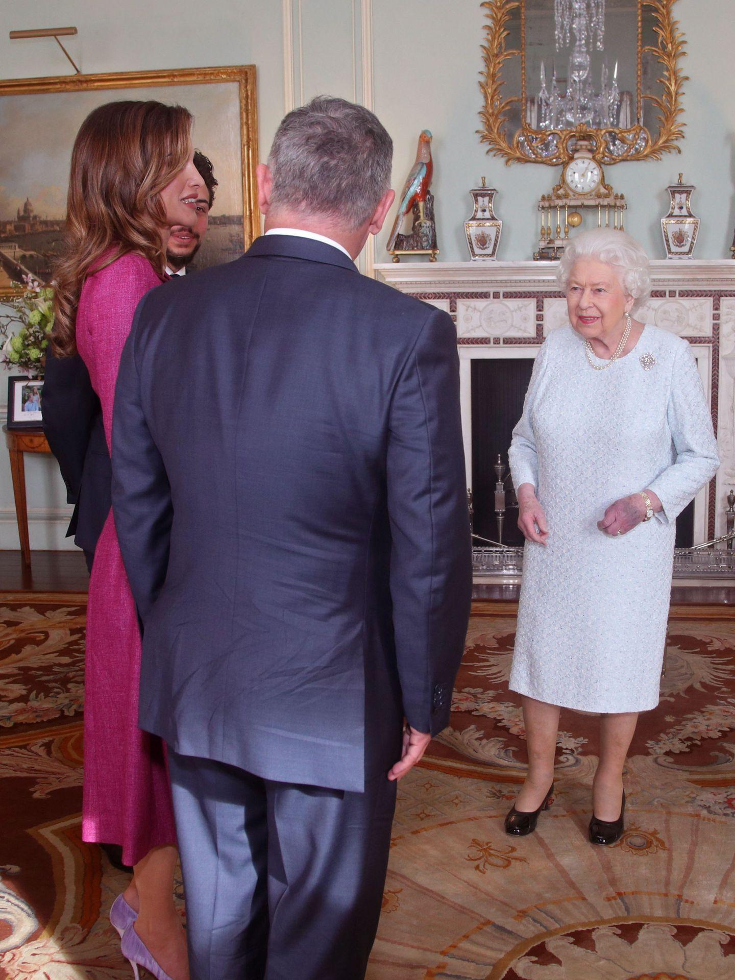 La reina Isabel, junto a los reyes de Jordania, con las manos amoratadas. (Reuters)