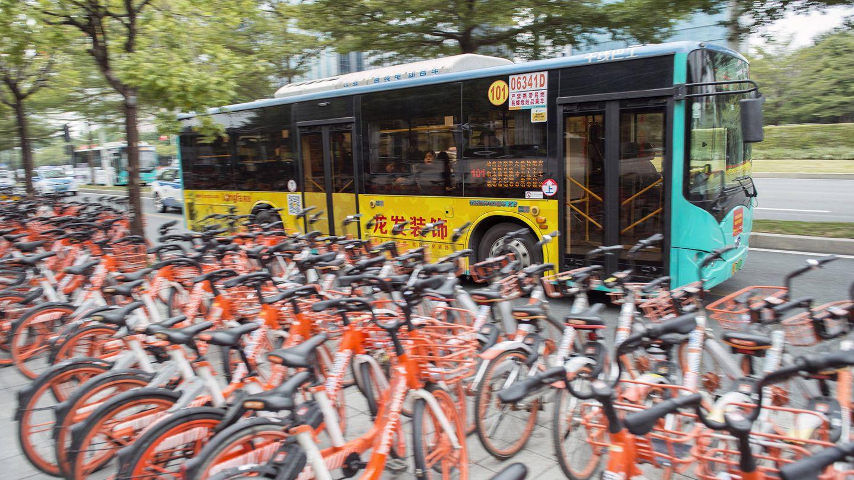Un autobús eléctrico pasa frente a un aparcamiento de bicicletas compartidas, otro avance en la movilidad de Shenzhen. (Z. Aldama)