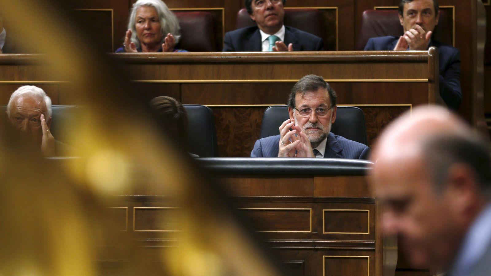 Foto: El presidente del Gobierno, Rajoy, al fondo mirando al ministro de Economía, Luis de Guindos. (Reuters)