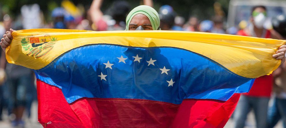 Foto: Un opositor al gobierno del presidente Nicolás Maduro sostiene una bandera de Venezuela durante una manifestación. (EFE)