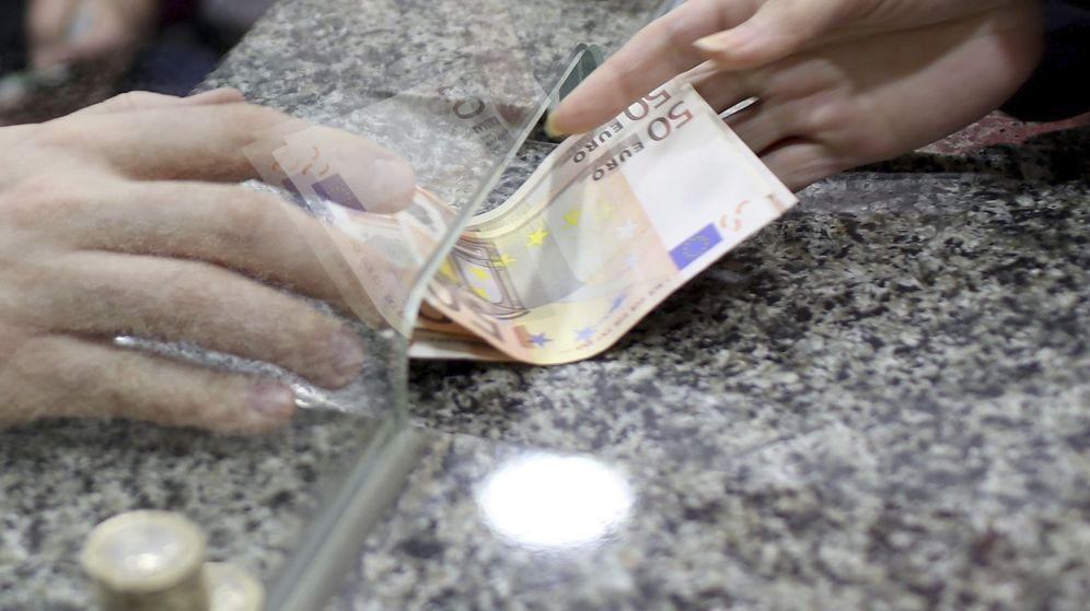 Foto: Un hombre cambia dinero en una oficina bancaria. (EFE)