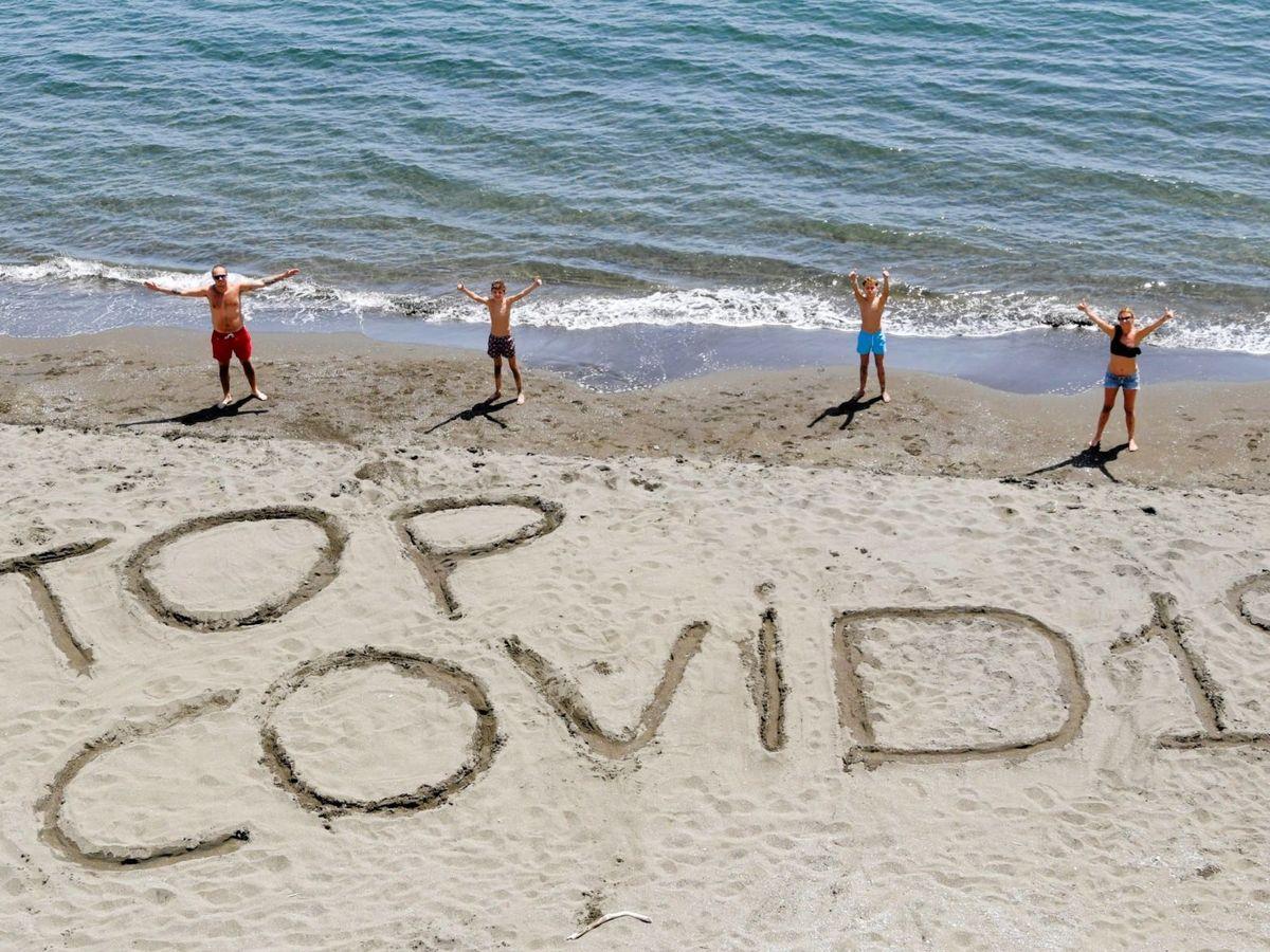 """Foto: Una familia escribe la frase """"Stop covid-19"""" en la arena de una playa de Nápoles, Italia. (EFE)"""