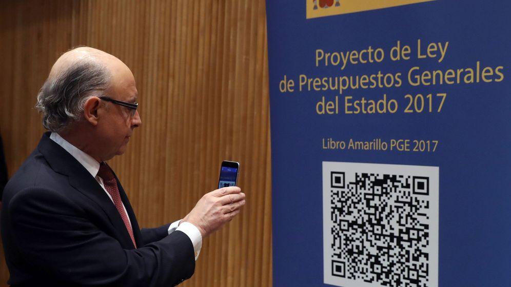 Foto: El ministro de Hacienda, Cristóbal Montoro, escanea con el móvl el código QR del proyecto de Ley de Presupuestos Generales del Estado. (EFE)