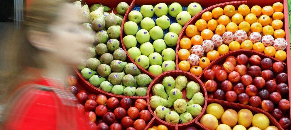 Foto: Una mujer pasa al lado de un expositor con frutas procedentes de España. (EFE)