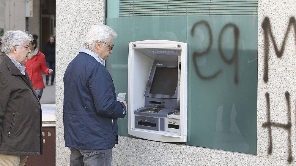 Foto: Dos hombres, ante un cajero de Bankia. (EFE)