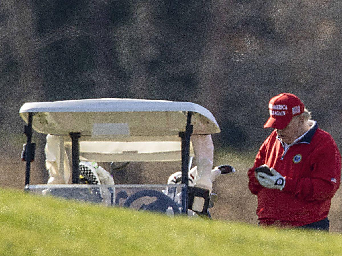 Foto: Donald Trump, jugando al golf y (quizá) tuiteando. (Getty)
