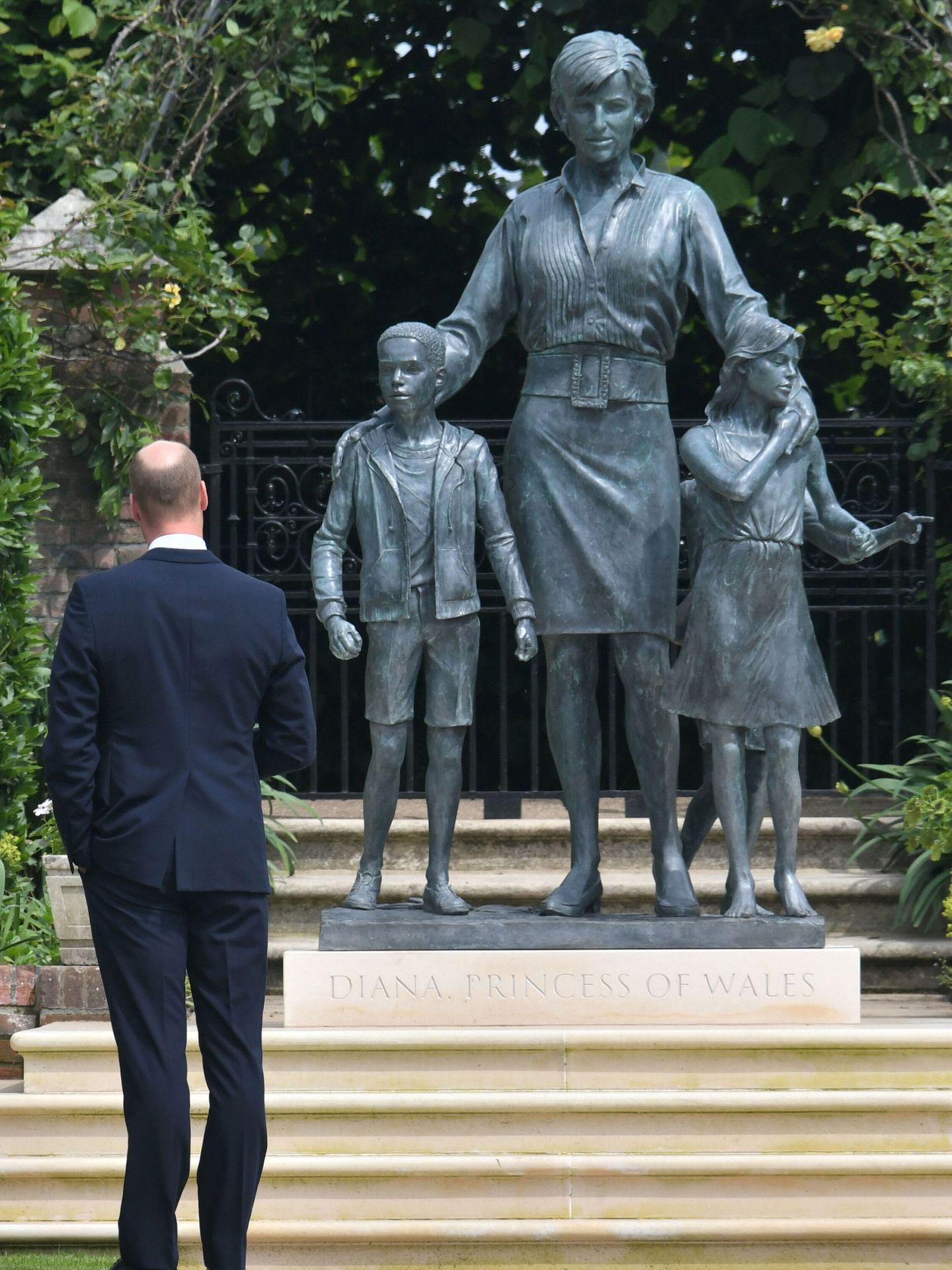 El príncipe William posa con la estatua de su madre. (Reuters)