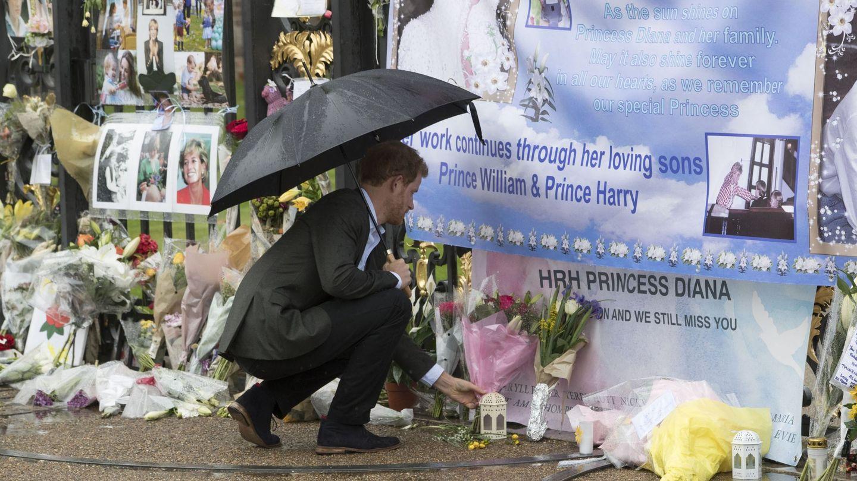 El príncipe Harry dejando flores en el exterior del palacio de Kensington, en homenaje a su madre. (EFE)