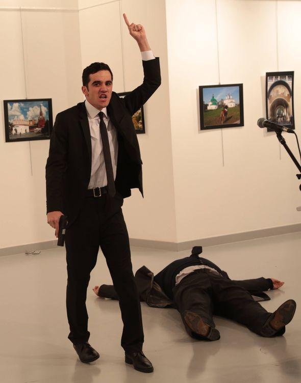 Foto: El asesino del embajador ruso en Ankara gesticula tras el ataque, en una galería fotográfica de la capital turca. (Gtres)