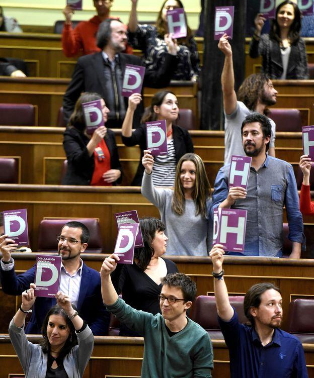 Foto: Los diputados de Podemos sacan carteles en favor de los derechos humanos durante el debate de la 'Ley 25'. (EFE)