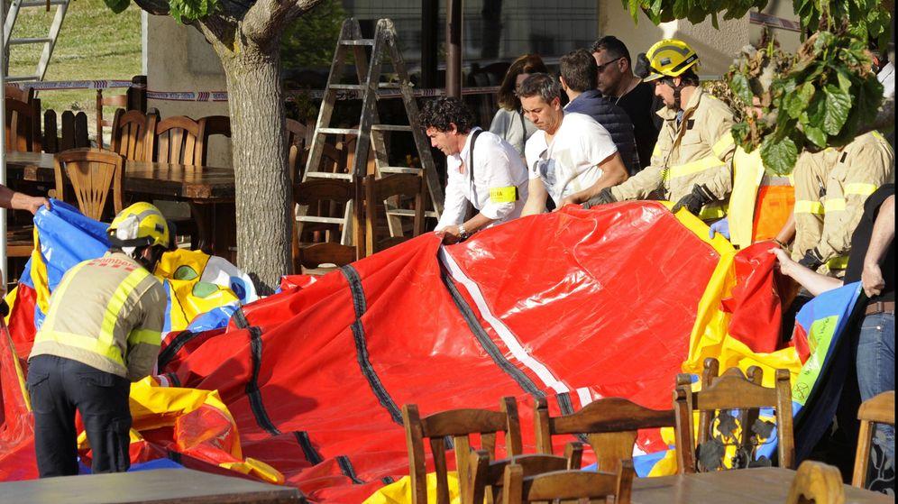 Foto: Varios operarios y bomberos retiran el castillo hinchable del restaurante Mas Oller. (EFE)