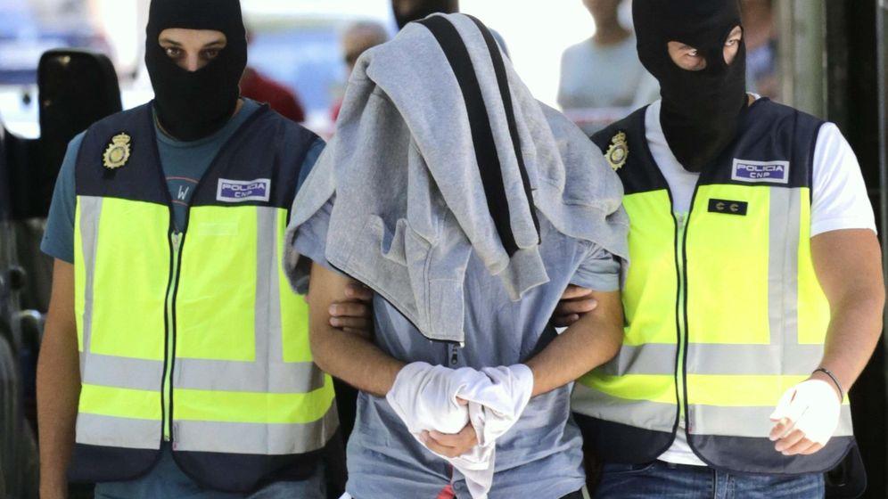 Foto: Agentes de la Policía Nacional conducen al detenido con la cabeza tapada. (EFE)