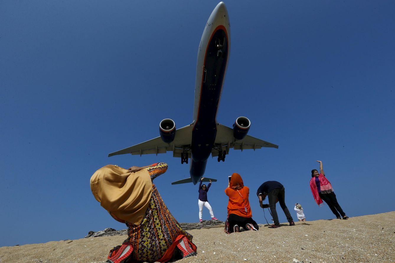 Foto: Turistas toman fotos en Playa Mai Kaho cuando un avión se acerca al aeropuerto de Phuket, en Tailandia, el 16 de marzo de 2016. (Reuters)