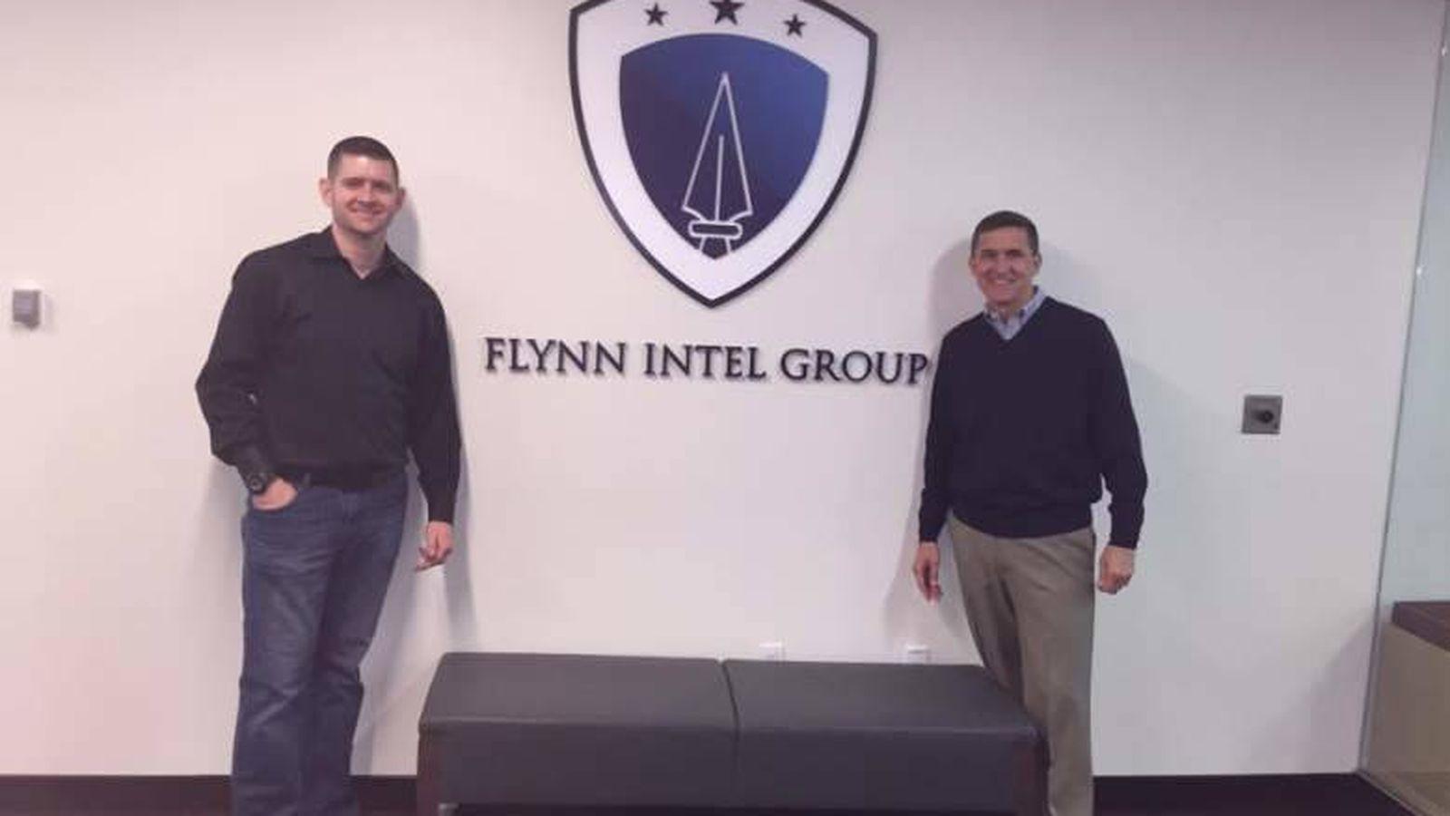 Foto: Michael Flynn y su hijo frente al logotipo del Flynn Intel Group