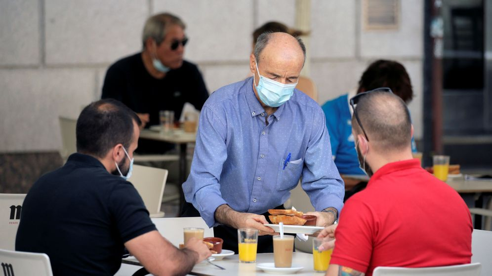Foto: Un camarero con mascarilla atiende en una terraza de Madrid. (Reuters)